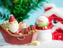 Happy Santa Claus with gifts box on the snow sled going to house. near house have Snowman and Christmas Tree. Santa Claus. And house on the snow. Christmas and Stock Image