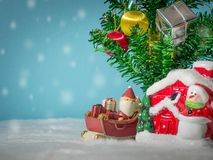 Happy Santa Claus with gifts box on the snow sled going to house. near house have Snowman and Christmas Tree. Santa Claus Royalty Free Stock Photography