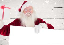 Happy santa claus holding blank placard and gift box. Against wooden background Stock Image