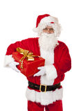 Happy Santa Claus holding Christmas gift in hands Stock Images