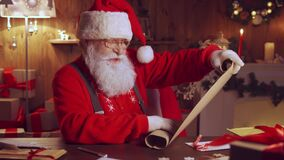 Happy Santa Claus holding parchment reading wish list sitting at home table.