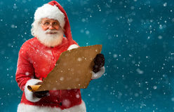 Happy Santa Claus holding vintage paper on blue background. Stock Photo