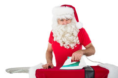 Happy santa claus ironing his jacket Stock Images