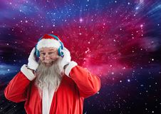 Happy santa claus listening music on headphones. Portrait of happy santa claus listening music on headphones against digitally generated background Royalty Free Stock Photo