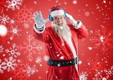 Happy santa claus listening to music on headphones. Happy santa claus listening to music headphones against digitally generated christmas background Royalty Free Stock Image