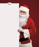 Happy Santa Claus looking out from behind the blank sign. On red background with copy space Stock Image