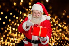 Happy Santa Claus offering present. Royalty Free Stock Photography