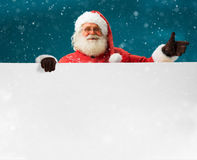 Happy Santa Claus pointing in white blank sign for your text with smile. / Merry Christmas & New Year's Eve concept / Closeup on blurred blue background Royalty Free Stock Image