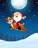 Happy Santa claus riding a reindeer in the night background Royalty Free Stock Photo