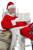 Happy santa claus showing bible Stock Photo