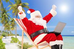 Happy Santa Claus sitting on a chair with laptop and gesturing h. Appiness, on a tropical beach Stock Images