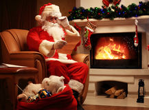 Happy Santa Claus sitting at his room at home near Christmas tree and big sack and reading Christmas letter or wish list Stock Photos