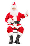 Happy Santa claus sitting on a wooden chair and giving a thumb u Royalty Free Stock Images