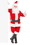 Happy Santa claus standing next to a billboard. Full length portrait of a happy Santa claus standing next to a blank billboard and giving a thumb up Royalty Free Stock Images