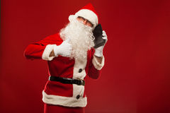 Happy santa claus talking on mobile phone and show Royalty Free Stock Image