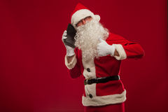 Happy santa claus talking on mobile phone and show okay gesture. Royalty Free Stock Images