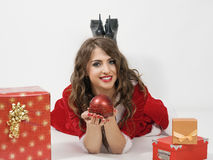 Happy Santa Clause woman holding sphere candle lying prone between gifts. Over gray studio background Stock Photo