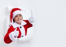 Happy santa costume boy leaning through paper hole - giving thum Stock Photo
