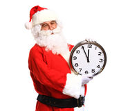 Happy Santa in eyeglasses pointing at clock showing five minutes. To Christmas Stock Image