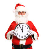 Happy Santa in eyeglasses pointing at clock showing five minutes. To Christmas stock images
