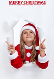 Happy santa girl at christmas pointing upwards to copy space Stock Photography