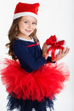 Happy santa girl is holding gift box with red Stock Photography