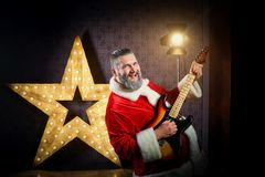 Happy Santa with a guitar is dancing against the background of a royalty free stock photo
