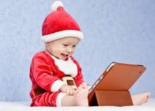 Happy santa helper baby boy with digital tablet Stock Photos
