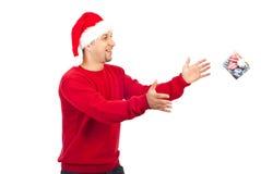 Happy Santa helper man catching small gift stock image
