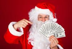 Happy santa holding dollars. Portrait of happy santa holding dollars over red background Stock Image