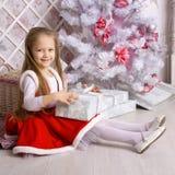 Happy Santa kid with gifts near the Christmas tree. Royalty Free Stock Photo