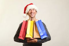 Happy Santa man holds shopping bags with christmas gifts. Christmas shopping, sales and discounts concept. Winter holidays. Man in. Christmas hat enjoying royalty free stock photography