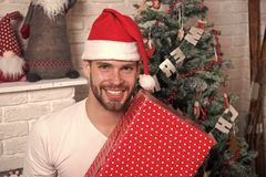 Happy santa man. man in santa hat hold christmas present. online christmas shopping. New year scene with tree and gifts stock photography