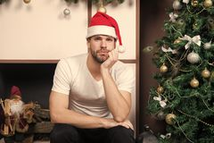 Happy santa man. online christmas shopping. New year scene with tree and gifts. delivery christmas gifts. man in santa. Hat wait for christmas present. The stock image