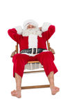 Happy santa relaxing on deckchair Stock Images