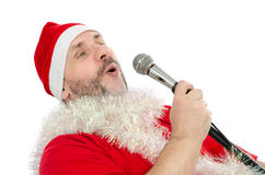 Perky Santa singing jingle bells. Perky man in Santa hat singing jingle bells at party Stock Photos