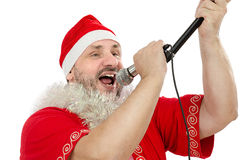 Happy Santa singing in microphone. Happy guy in Santa Suit Costume singing in microphone on a white background Stock Photo