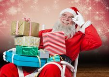 Happy santa sitting on chair with christmas gifts. Against digitally generated christmas background Stock Photos