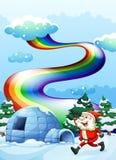 A happy Santa walking near the igloo under the rainbow Royalty Free Stock Photography