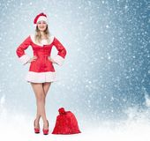 Happy Santa woman with full big red bag of gifts, on blue background and snow. stock image