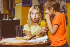 Happy or satisfied boy width girl eating pizza and Royalty Free Stock Images