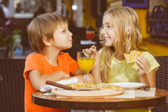 Happy or satisfied boy width girl eating pizza and Royalty Free Stock Image