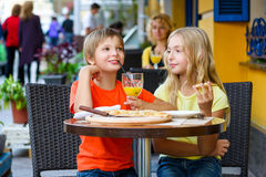 Happy or satisfied boy width girl eating pizza and Royalty Free Stock Photography