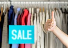 Happy and satisfied customer giving thumbs up in clothes store. Happy and satisfied customer giving thumbs up in a clothing store for good service or great stock images