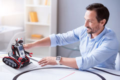 Happy and satisfied engineer testing robot in his science lab Stock Photo