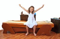 Happy and satisfied girl after a therapy. Girl sitting on a massage bed with arm wide open Stock Image