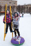 Happy and satisfied mother and child try to walk on stilts at winter. Social activities are at Maslenitsa holidays Royalty Free Stock Images