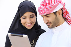 Happy saudi arab couple looking a tablet together. On a white wall background Royalty Free Stock Photography