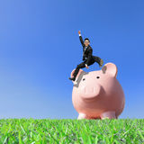Happy Saving Money. With my piggy bank - Young excited business man jump over piggy bank Royalty Free Stock Photography