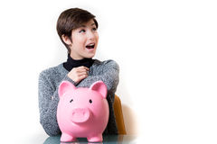 Happy about savings on a piggy bank. Young woman happy about savings on piggy bank, looking up and smiling on white isolated background copy space on the right Stock Photo
